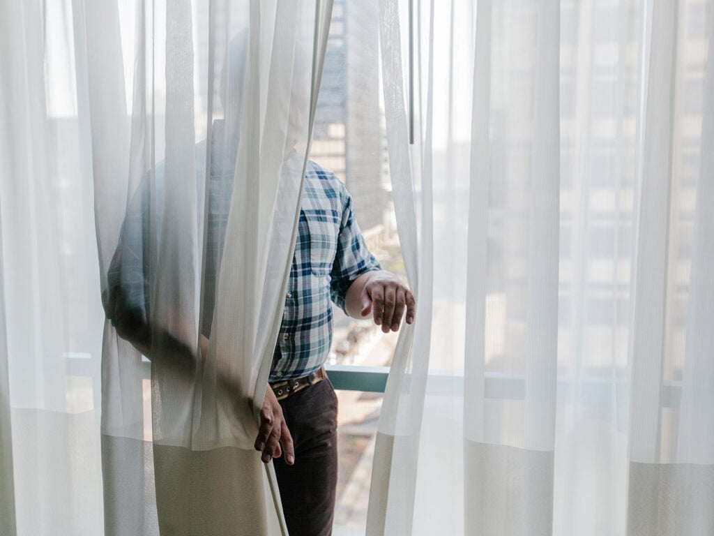 man hidden behind sheer curtain