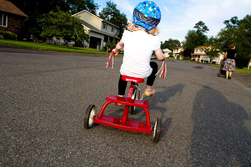 little girl on red tricycle from behind
