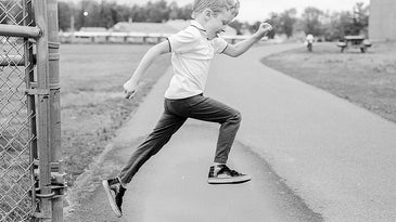 black and white photo of child jumping