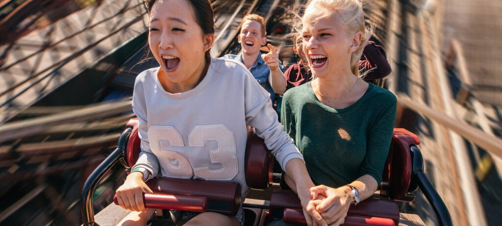 happy young people riding a roller coaster