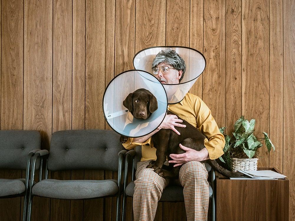 Man at Veterinarian Wearing Dog Cone
