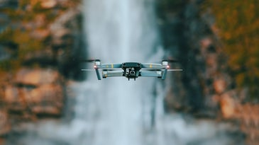 drone flying in front of waterfall