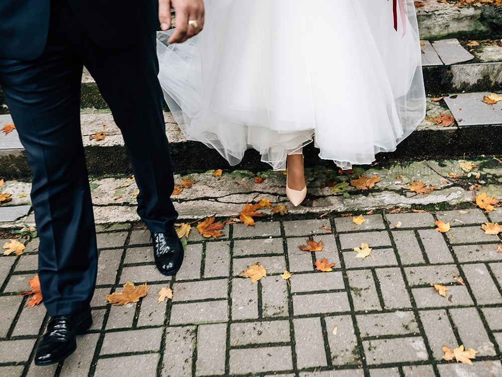 The bride and groom walk along the autumn leaves