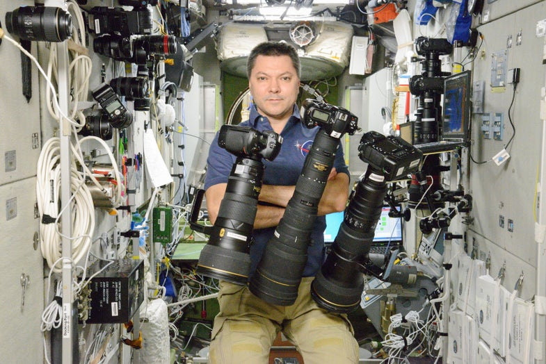 Russian Astronaut Poses With Floating Nikon Cameras on the International Space Station