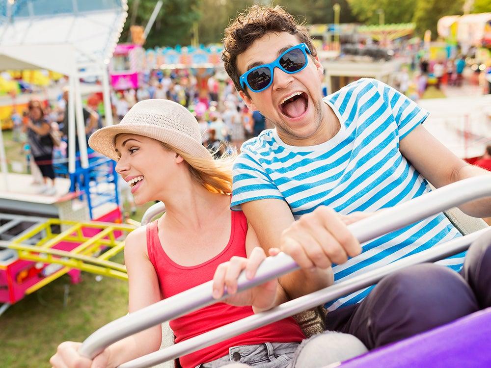 couple at fun fair riding roller coaster