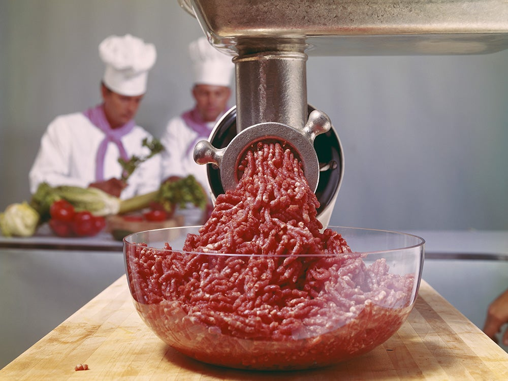 Minced meat coming through mincer with chefs in background