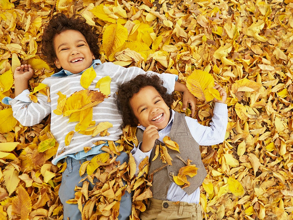 Twins laying in yellow autumn leaves