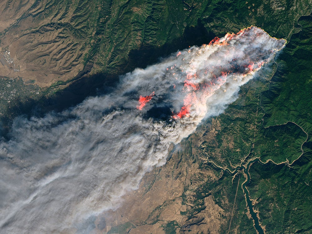 a satellite view of a massive plume of smoke and fire