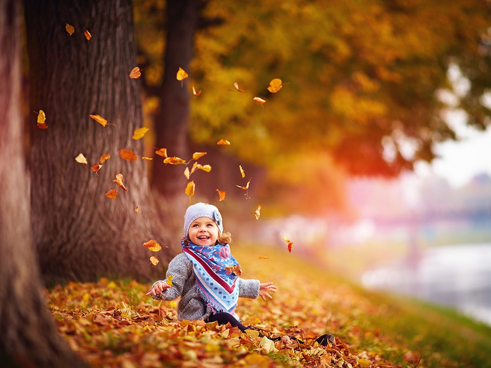 Adorable happy baby girl throwing the fallen leaves up, playing in the autumn park