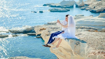 married couple taking selfie on a cliff