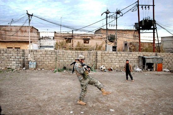 """""""A-U.S.-soldier-tries-to-play-soccer-with-Iraqi-chi"""""""