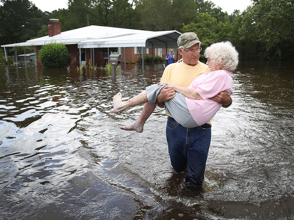 elderly man carrying wife through flood