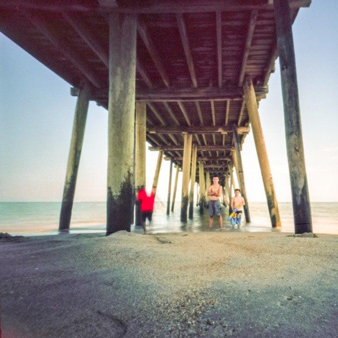 sample photo of boys under a beach pier