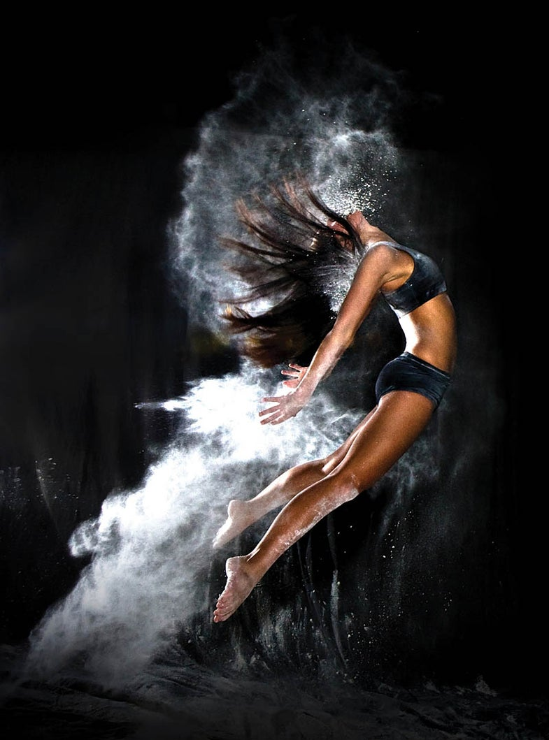 woman jumping and throwing flour