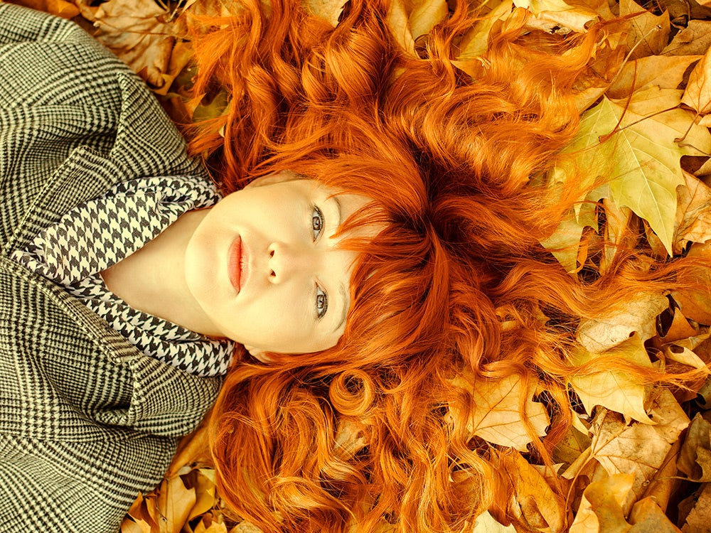 Close-Up Portrait Of Young Woman Lying On Dry Fallen Leaves