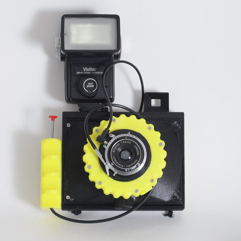 Yellow Cameradactyl OG 4x5 hand camera with flash