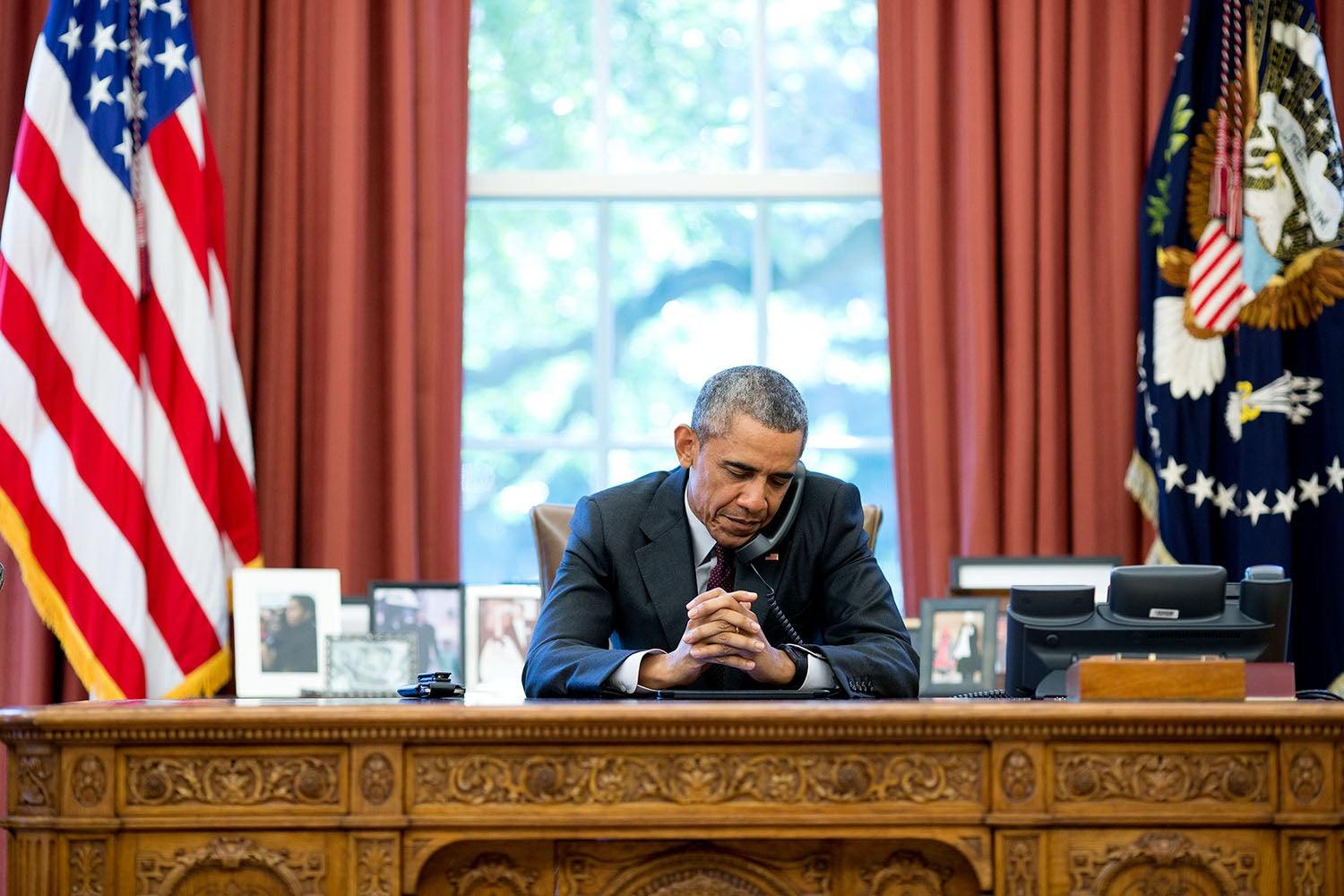 President Obama listens to a prayer during a phone call