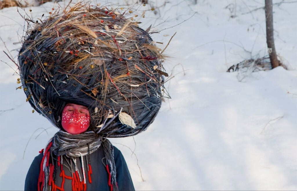 woman painted red with giant nest on her head