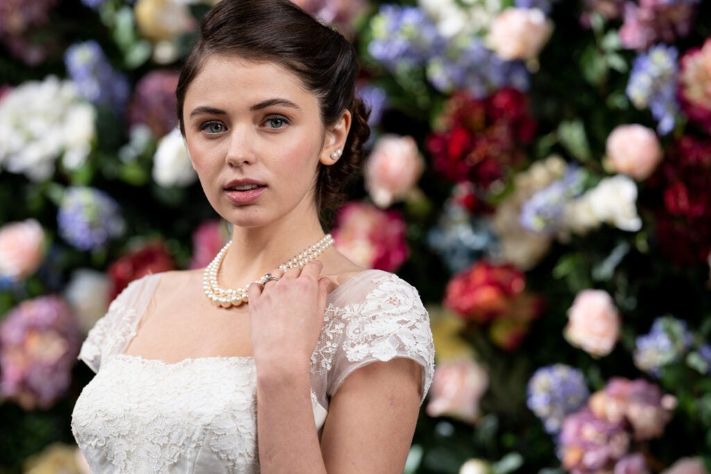 model in white against flower wall