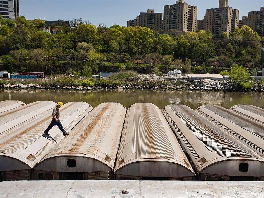 man walking on top of subway cars