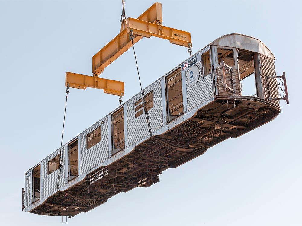 crane lifting a subway train