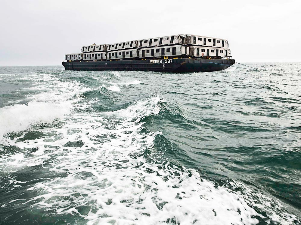 barge on the ocean carrying subway train cars