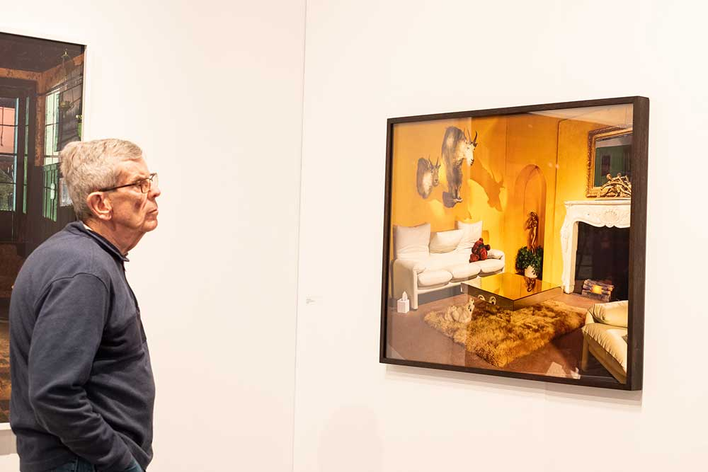 man looking at photograph on the wall