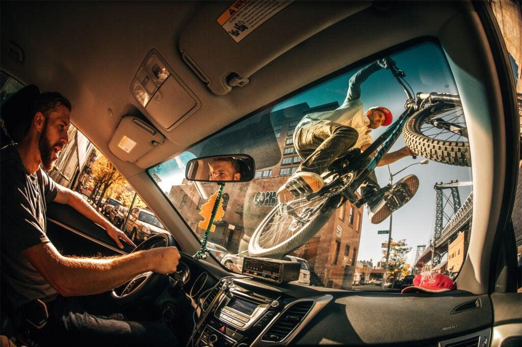 Bike rider over car