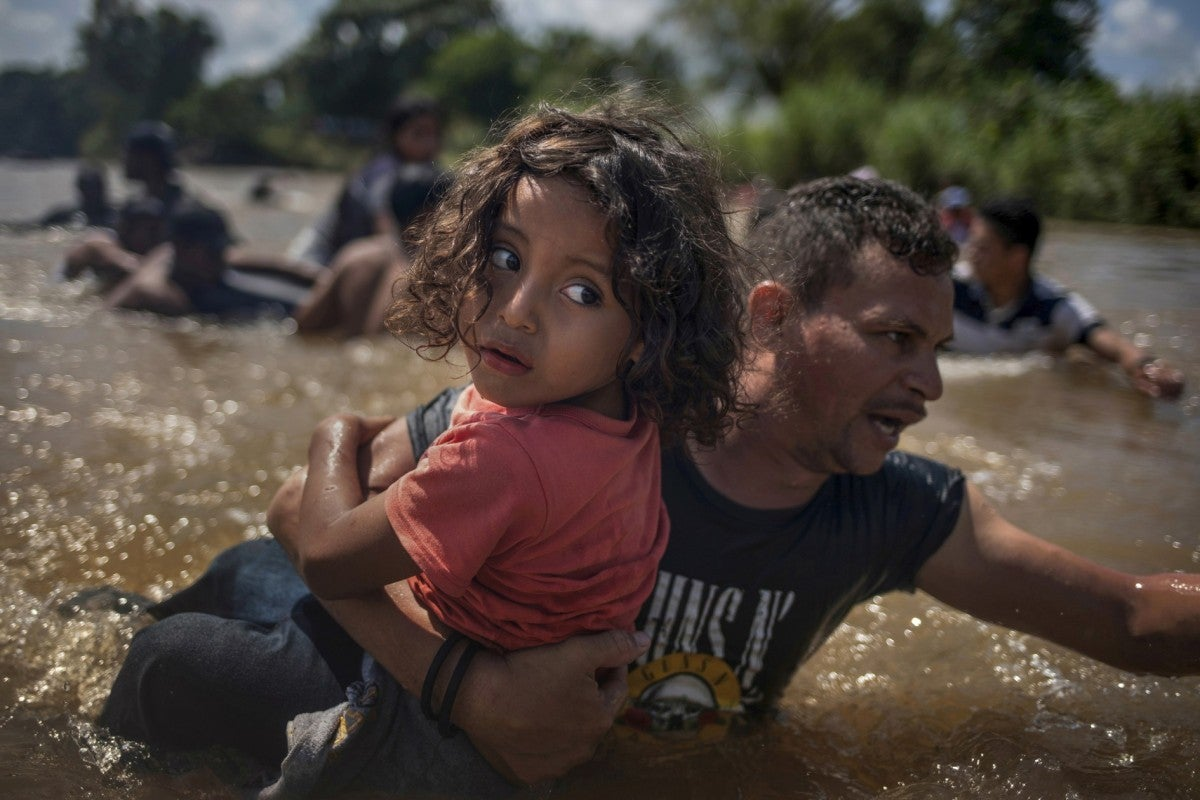 child being carried across shallow water