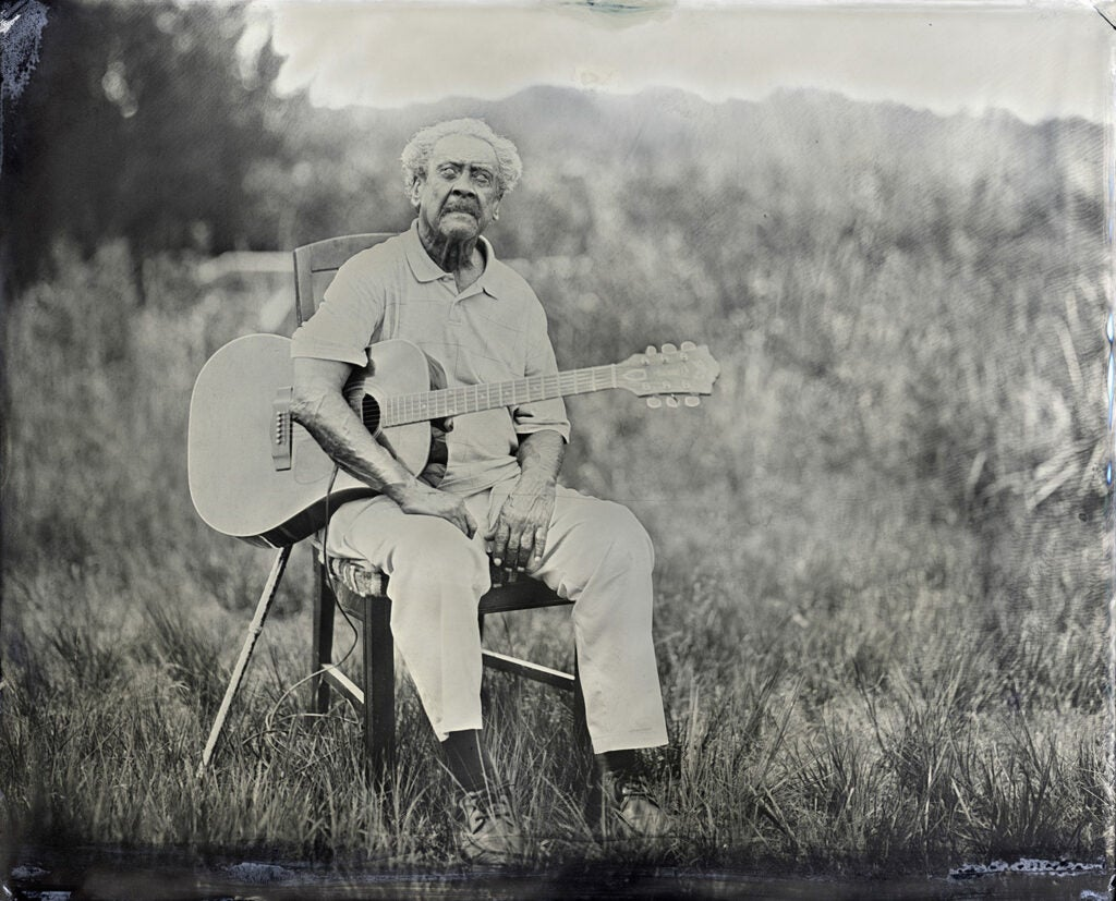 Boot Hanks with guitar in a field