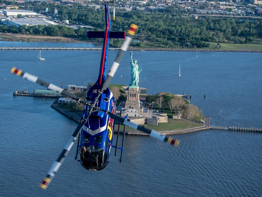 Redbull helicopter performing stunts with the Statue of Liberty in the background