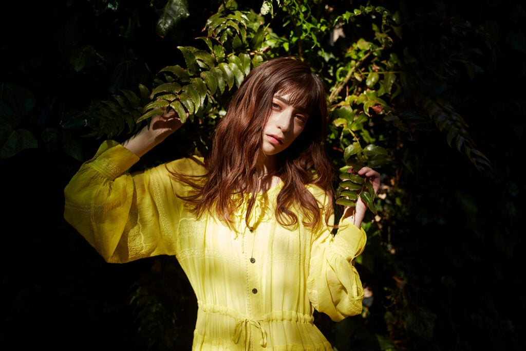 girl against greenery with yellow dress