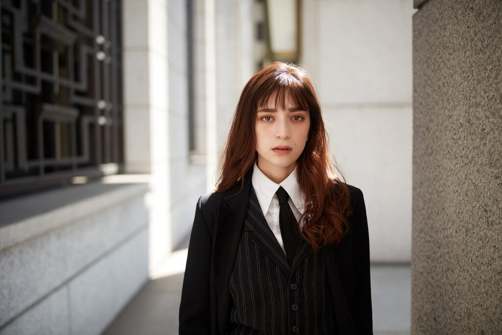 girl in black tie with red-brown hair