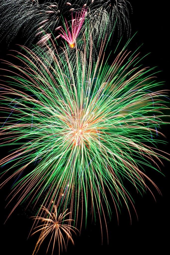 green and orange fireworks against black