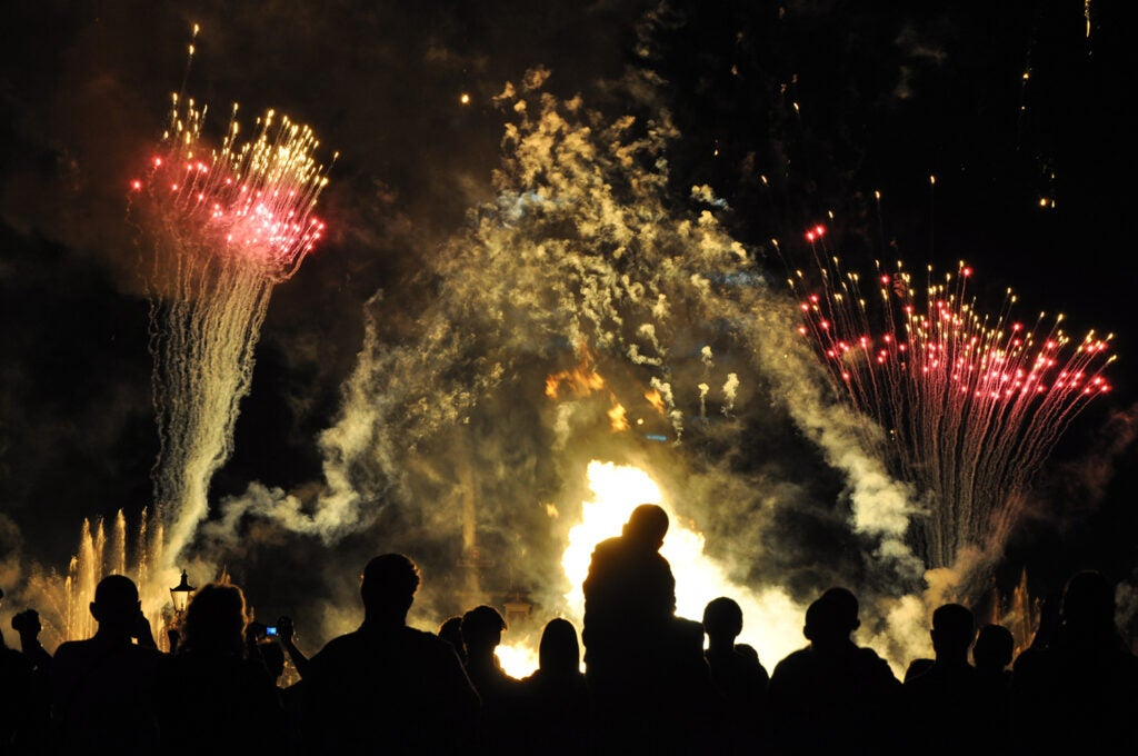 humans silhouetted against fireworks display