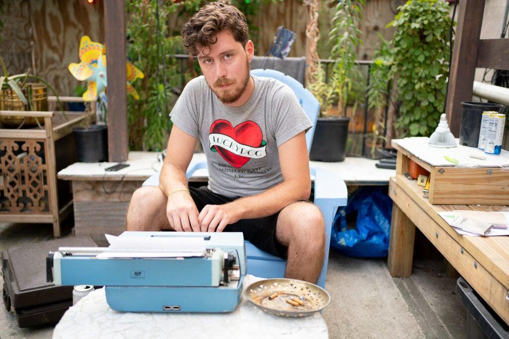 man sitting with blue typewriter