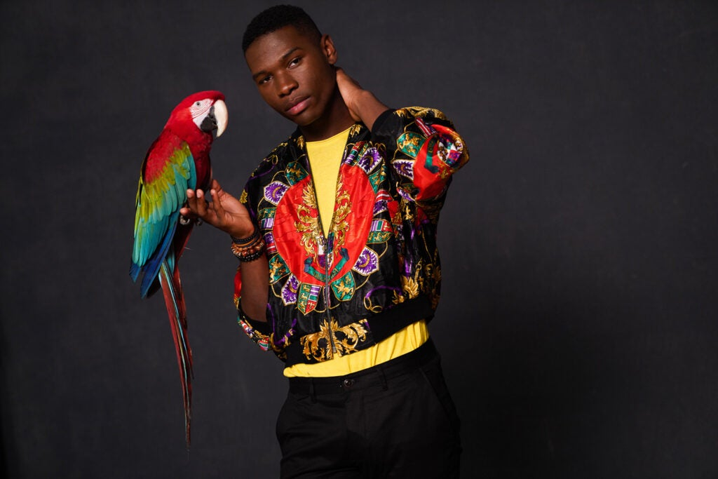 man in colorful jacket with macaw