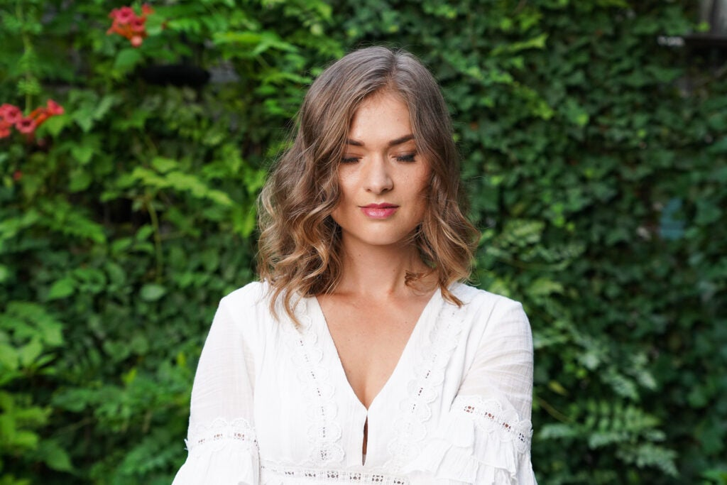 woman in white blouse against leafy backdrop