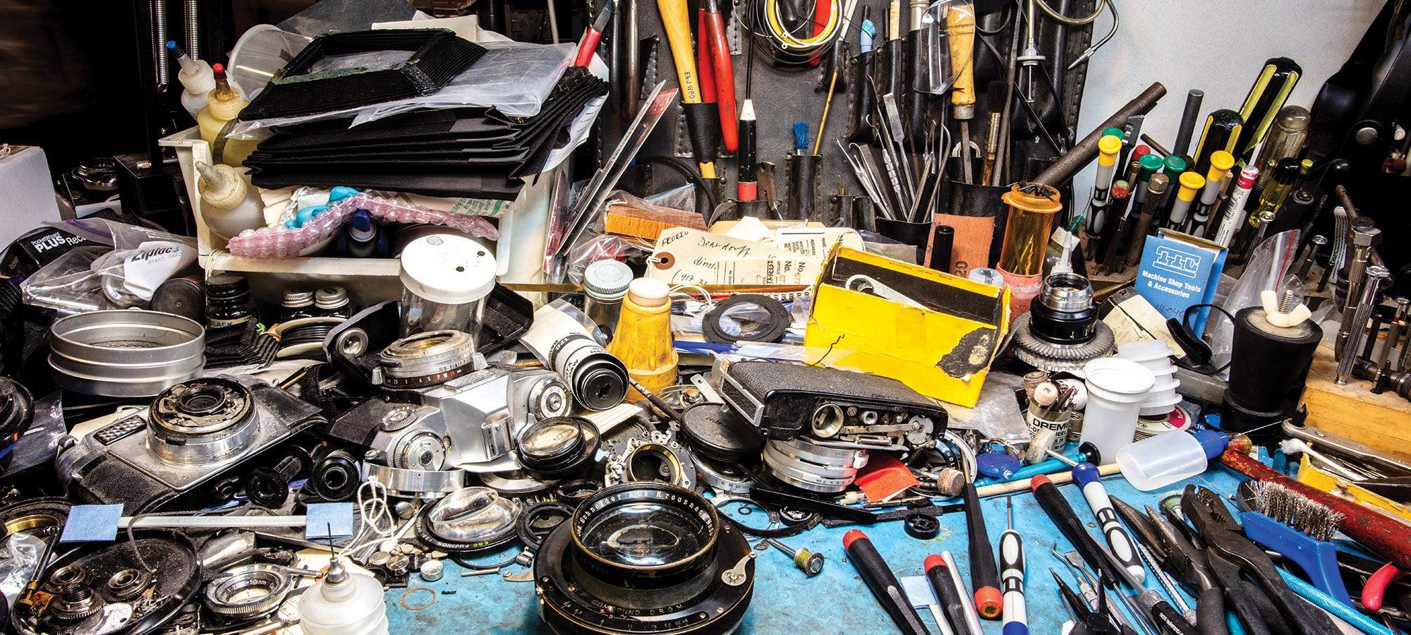 Husks of vintage film cameras and lenses littering workbench