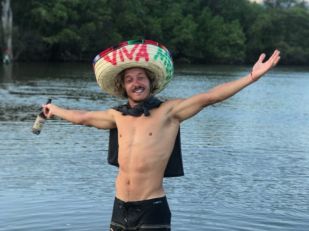 Shirtless man in the water with sombrero and a beer