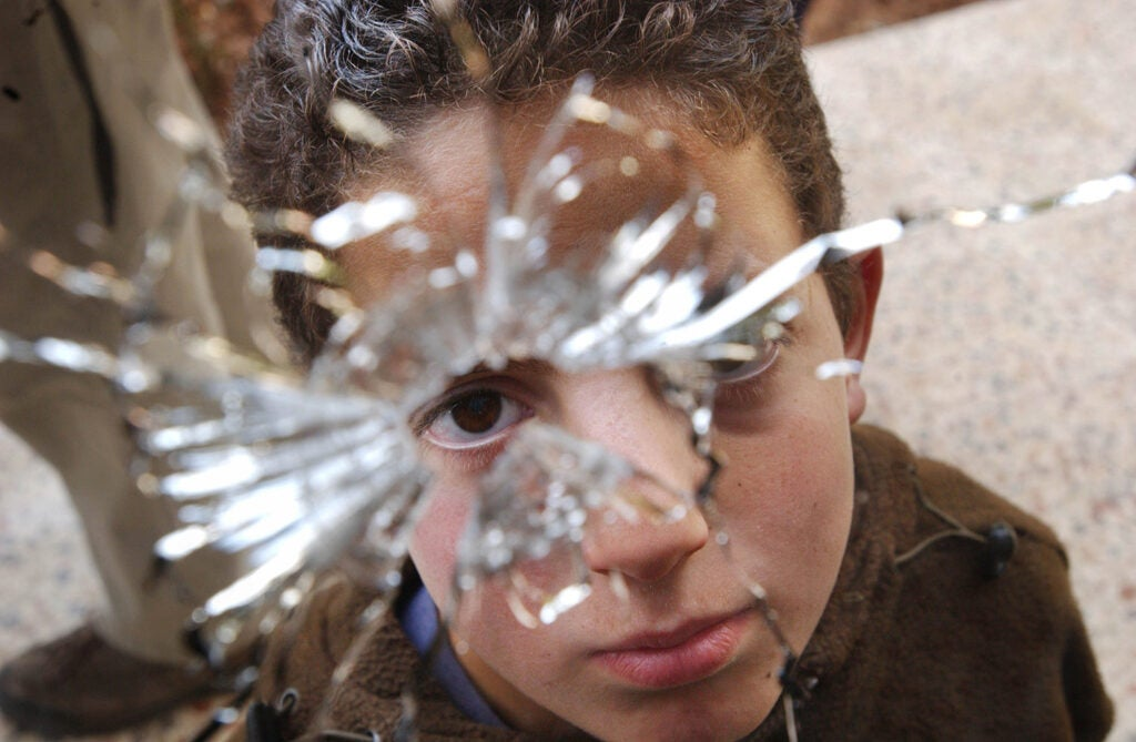 child looking through bullet hole