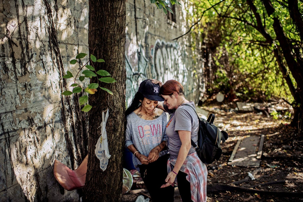 outreach worker consoling friend in the Bronx