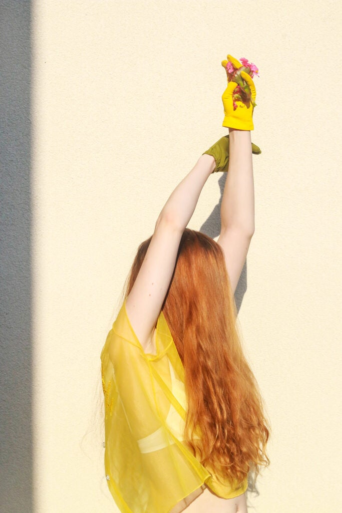 girl in yellow with red hair and yellow glove holding flowers