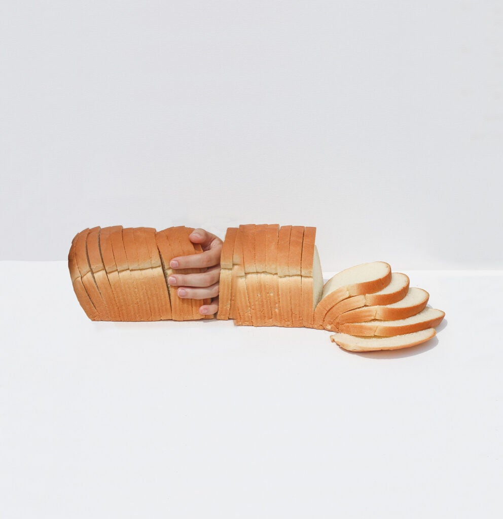 hands in loaf of bread on white background