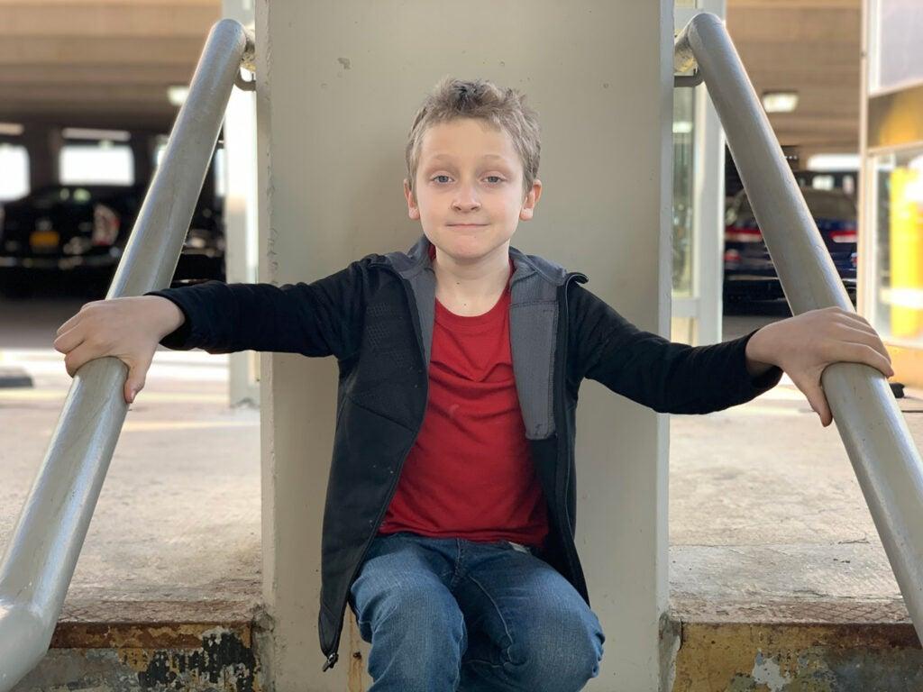 A boy in a jacket sitting down