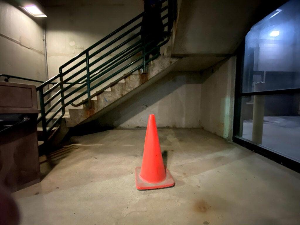 An orange cone under a staircase
