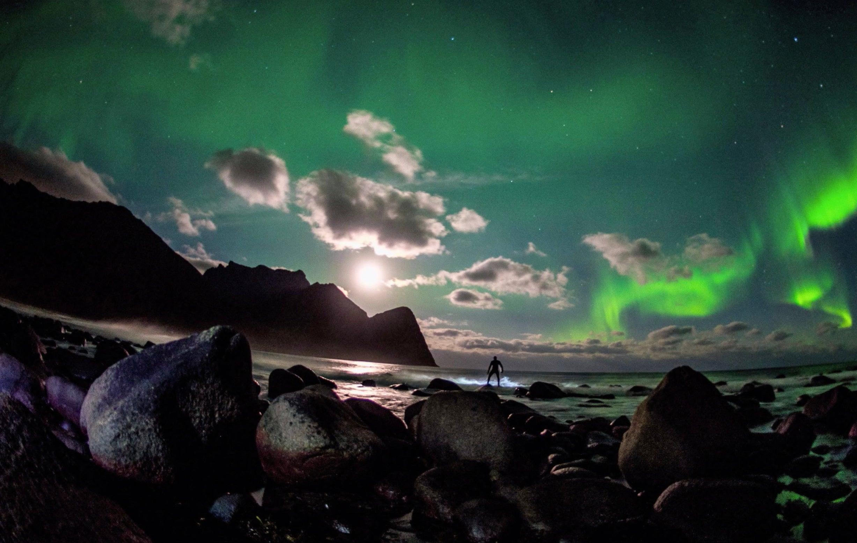 surfer beneath the northern lights green sky