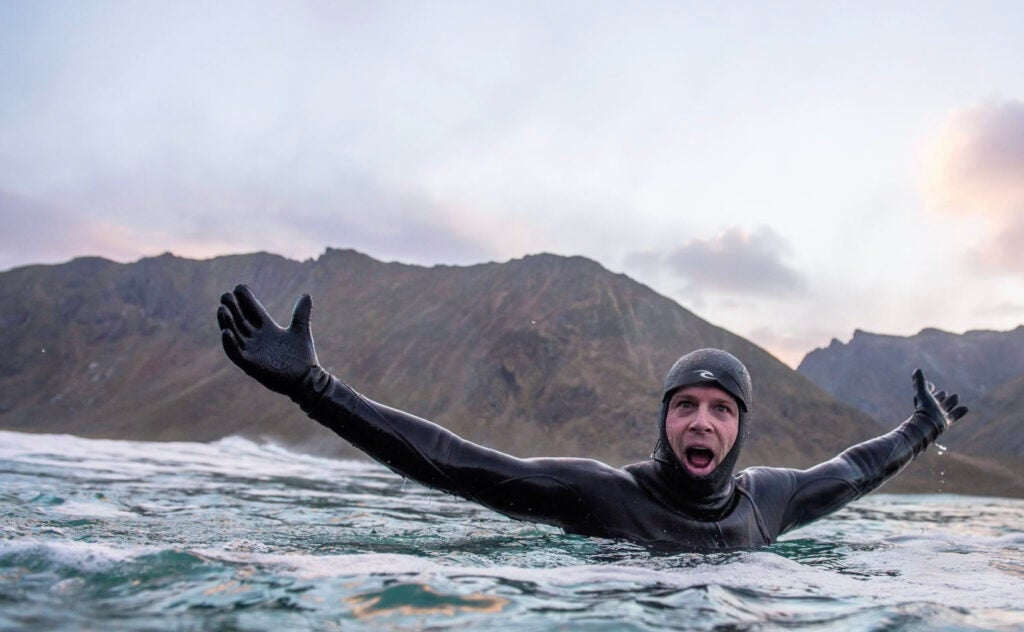 surfer Mick Fanning swimming in wetsuit