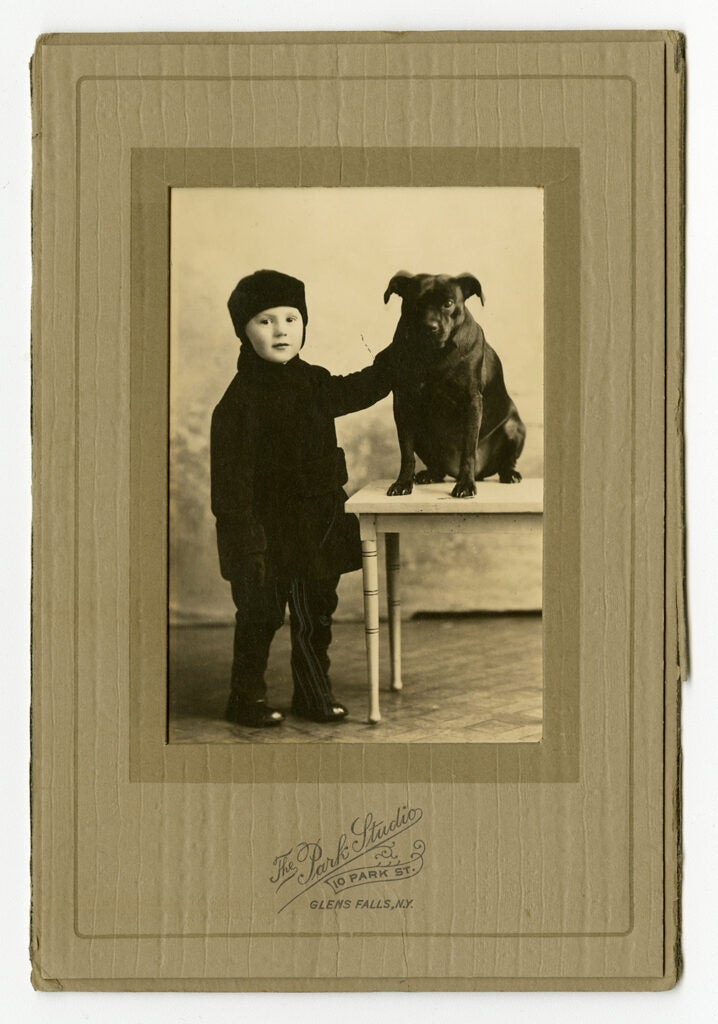 vintage photo of child in cap with dog