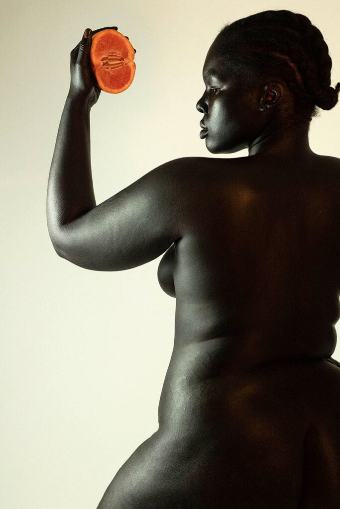 dark skinned woman holding fruit in front of her
